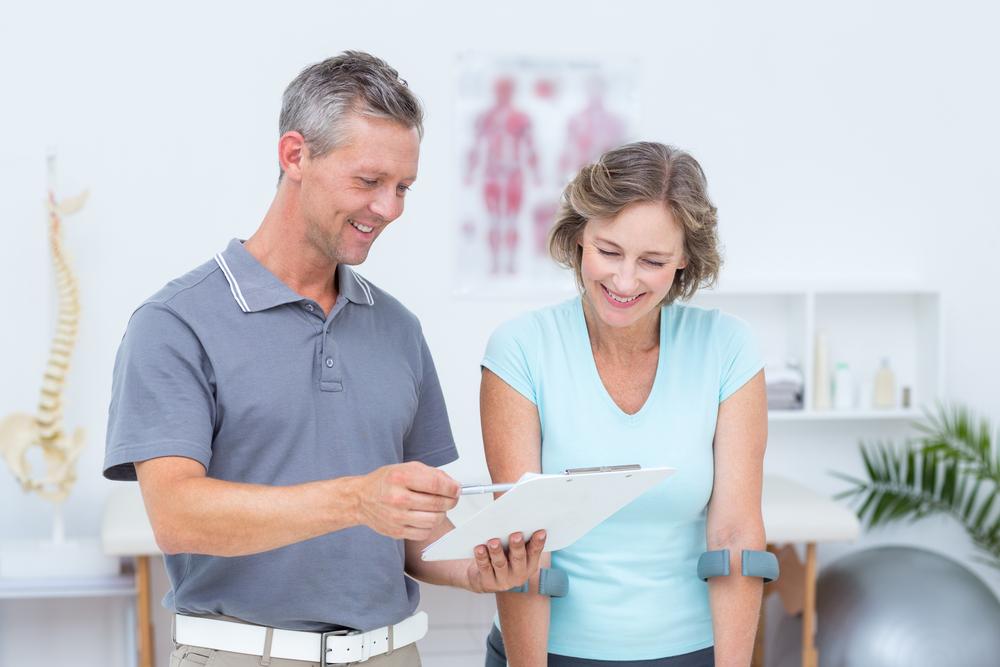 Fisioterapeuta com prancheta e paciente